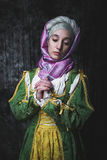 Medieval woman holding hands in prayer. Pray. In the old beautiful yellow-green dress. Historic image. Gothic. Europe.anachronism Stock Photo