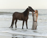 Medieval woman and horse in water. Time exposure with flowing water Stock Images