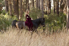 Medieval woman riding horse. Through forest Royalty Free Stock Photo