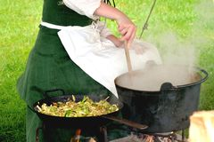 Medieval woman stirring pot Royalty Free Stock Photo