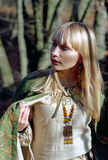 Medieval woman walking in forest Stock Image
