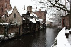 Medieval wooden and brick buildings at canal street in Bruges, Belgium. Winter landscape of old historical town in Europe. Winter travel landscape. Christmas Royalty Free Stock Photo