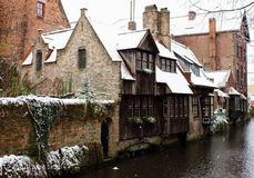 Medieval wooden and brick buildings at canal street in Bruges, Belgium. Winter landscape of old historical town in Europe. Winter travel landscape. Christmas Royalty Free Stock Images