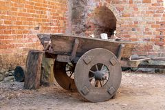Medieval wooden cart. In the castle. Bricks wall in the background royalty free stock photos