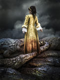 Medieval young girl surrounded by crocodiles Stock Photography