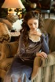 a medieval young lady sits in a cozy antique sofa chair in an old-fashioned interior modestly downcast eyes Stock Photography