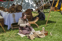 Medieval Young Woman Spinning Wool. Nogent le Rotrou,France, 11.05.2013: Medieval young woman spinning wool outside of the tent during the Percheval Medieval Royalty Free Stock Photos