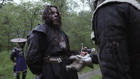 A man with a zombie makeup is pretending to be stabbed by a sword