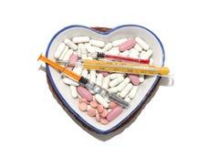 Medikamente in einer Porzellanschale in Form eines Herzens Stockbilder