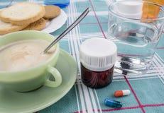 Medikation während des Frühstücks, Kapseln nahe bei einem Glas Wasser, Begriffsbild stockbild