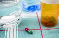 Medikation während des Frühstücks, Kapseln nahe bei einem Glas Wasser, Begriffsbild lizenzfreies stockfoto