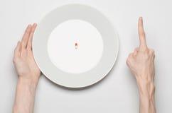 Medikationen und unsachgemäßes Nahrungsthema: menschlicher Handgriff eine Platte mit den Pillen lokalisiert auf Draufsicht des we Lizenzfreie Stockbilder