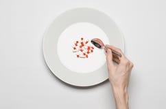 Medikationen und unsachgemäßes Nahrungsthema: menschlicher Handgriff eine Platte mit den Pillen lokalisiert auf Draufsicht des we Lizenzfreie Stockfotografie