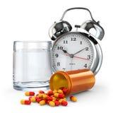Medikationszeit. Pillen, Wasserglas und Wecker. Stockfoto