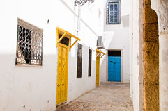 Medina streets in Tunis. A typical mediterranean street in Tunis old city, with white wall and colored doors Royalty Free Stock Photography