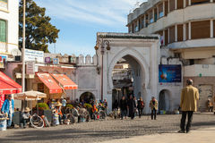 Medina of Tangier, Morocco. Ordinary people walking on street. TANGIER, MOROCCO - MARCH 23, 2014: Ancient gate to Medina of Tangier, Morocco. Ordinary people Royalty Free Stock Photography