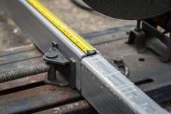 Medindo um metal com fita de medição imagens de stock