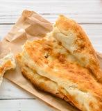 medio caucásico quebrado del pan Pita, mintiendo en una tabla de cortar Fondo de madera ligero Foto de archivo libre de regalías
