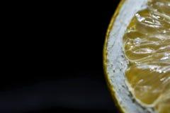 Medio detalle en un fondo negro, cierre de la rebanada del limón para arriba, aislado fotografía de archivo libre de regalías