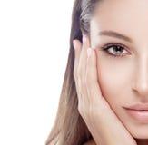 Medio estudio de la cara de la mujer hermosa en blanco con los labios atractivos aislados en el blanco que toca su cara con los f Fotografía de archivo libre de regalías