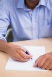 Medio hoofdstuk van zakenman het schrijven document bij bureau royalty-vrije stock afbeeldingen