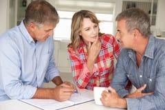 Medio leeftijdspaar met financiële adviseur thuis Stock Foto