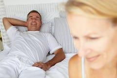Medio leeftijdspaar op bed Stock Afbeeldingen