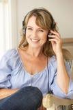 Medio leeftijdsvrouw die aan muziek luistert Stock Foto