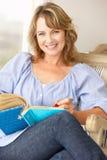 Medio leeftijdsvrouw die in notitieboekje schrijft Stock Afbeelding