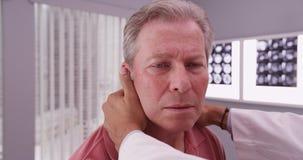 Medio oude mannelijke die geduldig hebbend hals door medische arts wordt onderzocht stock foto's