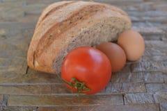 medio pan de la harina negra con las semillas tomate y huevos Imagen de archivo