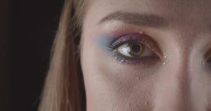 Medio retrato de la cara del primer de la hembra de pelo corto caucásica joven con los ojos con el maquillaje bonito del brillo q almacen de metraje de vídeo