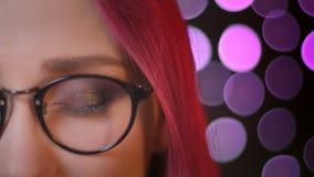 Medio retrato de la cara del primer de la muchacha caucásica bonita joven con el pelo teñido rojo en los vidrios que miran la cám almacen de metraje de vídeo