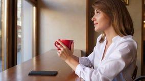 Medio retrato de la cara de la mujer joven de consumición del café almacen de metraje de vídeo