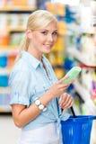 Medio retrato de la longitud de la muchacha en la tienda que elige los cosméticos Foto de archivo