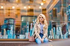 Medio retrato de la longitud de la mujer atractiva con el pelo rubio hermoso que espera alguien mientras que se sienta solamente  Foto de archivo libre de regalías