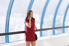 Medio retrato de la longitud de una mujer imponente feliz que tiene una conversación telefónica mientras que se coloca en interio Foto de archivo libre de regalías