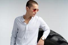 Medio retrato de la longitud del hombre joven hermoso en gafas de sol rojas, camisa blanca que lleva, inclinada en el neum?tico g fotos de archivo