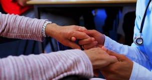 Medio sectie die van vrouwelijke arts droevige gehandicapte hogere vrouw troosten bij verpleeghuis 4k stock video