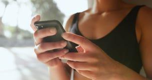 Medio sectie van jonge Afrikaanse Amerikaanse vrouw die mobiele telefoon in de stad 4k met behulp van stock video