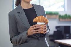 Medio sectie van vrouwelijk uitvoerend holdingskoffie en croissant stock foto