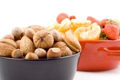 Medio tazón de fuente con las frutas y las tuercas mezcladas fotografía de archivo