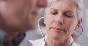Medio-verouderde arts die aan mannelijke patiënt spreken royalty-vrije stock afbeelding