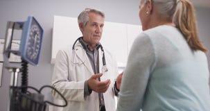 Medio-verouderde arts die aan vrouwelijke patiënt spreken stock foto's