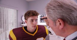 Medio-verouderde arts die voetbalster na schok onderzoeken stock afbeeldingen
