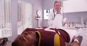 Medio-verouderde fysiotherapeut die de sporten van de universiteitsatleet inj onderzoeken stock afbeelding