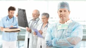 Medio-volwassen chirurg met medisch team op achtergrond Royalty-vrije Stock Afbeeldingen