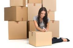 Medio volwassen gelukkige vrouw tijdens beweging met dozen bij nieuwe vlakte Stock Foto's
