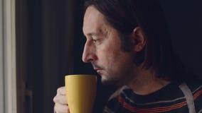Medio volwassen Kaukasische mens die en een kop thee ontspannen drinken, die uit venster kijken stock videobeelden