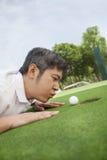 Medio volwassen mens die in een golfcursus liggen die de bal in het gat proberen te blazen Royalty-vrije Stock Afbeeldingen